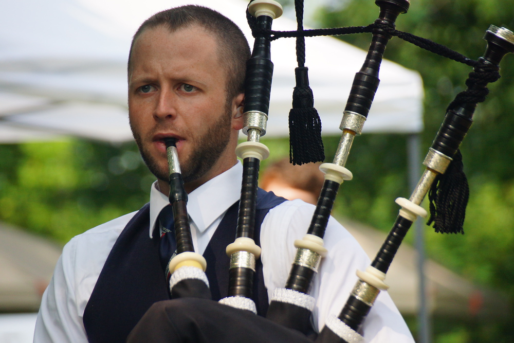 A close up shot of a man playing the bagpipes at the Highland Games
