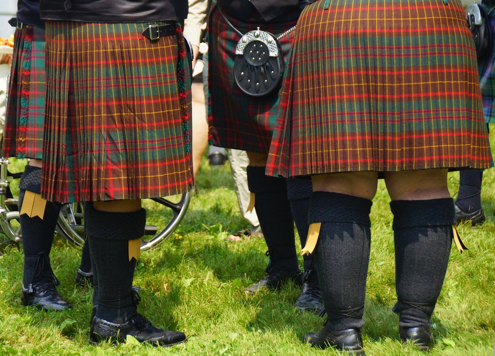 A group of men wearing kilts form in a circle to socialize at the New Brunswick Highland Games in Fredericton, Canada.