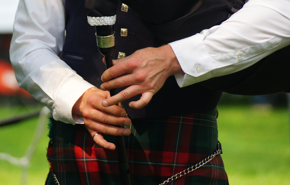 A close up shot of the hands of a talented bagpipe performer