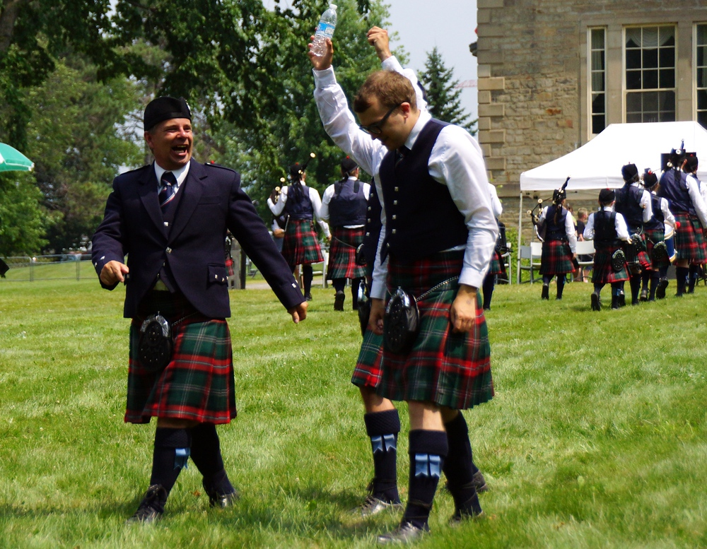 Men sharing a laugh as the walk along the grass at the New Brunswick Highland Games in Fredericton