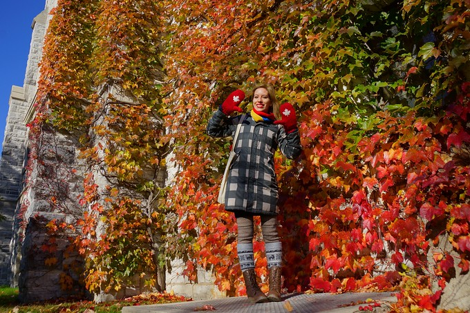 Audrey Bergner standing by the colorful leaves and ivy at Queen's University in Kingston, Canada