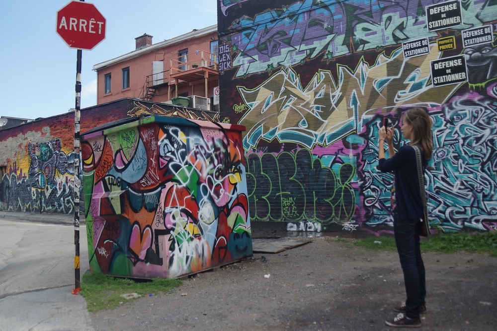Audrey Bergner taking a photo of Montreal street art and graffiti