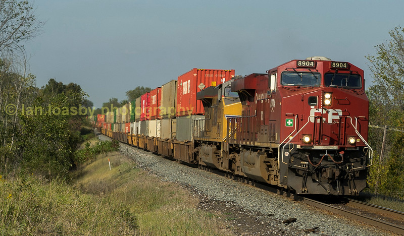 This is GP train 112 a class one  intermodel service from Vancouver  - Montreal  and runs daily .  CP # 8904 a Gevo powered ES 44AC  heads the train with Union pacific GMD SD70 #5328 behind it .  The location is Allison station mactier sub Tottenham Ontario