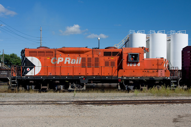 Shooting this photo with a Canon 40D which happens to have a live view function, I had to hold the camera over my head to get it over a fence to capture this photo of CP 1694, a GMD GP 9u.<br /> <br /> Photo taken at the CP Dryden yard.