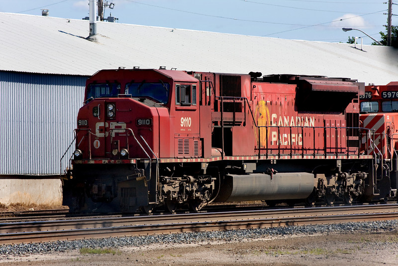 CP 9110, a GMD SD90MAC sits in the Dryden yard with a SD-40-2 (CP 5976) trailing. These units where the power of a (rail) work train.<br /> <br /> Using the live view function of the Canon 40D, I had to hold the camera over my head to shoot between two strands of barbed wire on top of a fence to get this shot. I couldn't get too much of the second unit as there was a tree in the way - as evident of a dark shadow above the second unit.