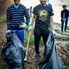 From left, UMass Lowell students, Kiran Rao and Mohamed Ibrahim help clean up the canal behind the Boot Mills. SUN/Caley McGuane