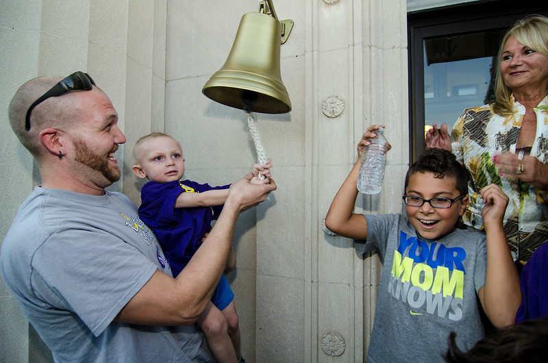 Dexter Turner, 3, held up by dad Ricky Turner, rings a bell at Leominster City Hall signifying his battle with cancer. SENTINEL & ENTERPRISE / Ashley Green
