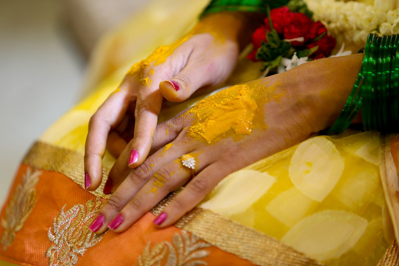 Relatives and guests apply Haldi on the bride's hands and face on her wedding day