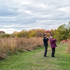 Looking out the back window of at the exhibit, I noticed the nice large field of tall grass, and the wonderful fall colors behind it, and Ricia said we could go out and tour it after she was done touring the various wood carving artists.<br /> <br /> I liked this pathway cut into the tall grass, but as nice as it was these roads tend to look rather empty when none is in it, but as Ricia and I continued to chat a pair of bird watchers happened by to fill in the scene nicely.