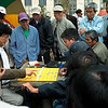 When I finally managed to slip into an opening, I guessed that at heart of this scene was the age old man vs. machine saga played out here in 2009 at this quaint little park in Chinatown. It appeared that the opponent on the right, strumming his playing pieces, was using that mini laptop to chart every move he and his opponent on the left made. The gentleman on the left on the other hand, just used his brains, and at times gave the crowd animated comments on his strategy, while his opponent remained pretty much silent throughout.<br /> <br />  Not knowing the game it's hard for me to say who was winning and by how much. Originally I thought the opponent on the left had to make a big comeback because I didn't see a lot of his men on the board, but it turned out several of his pieces were blocked from my view, and when I reviewed my shots later, by the number of remaining pieces, the battle seemed very even throughout. The crowd certainly seemed to remain transfixed throughout this match between this jovial fellow and his quiet studious opponent, seeking an advantage through technology.