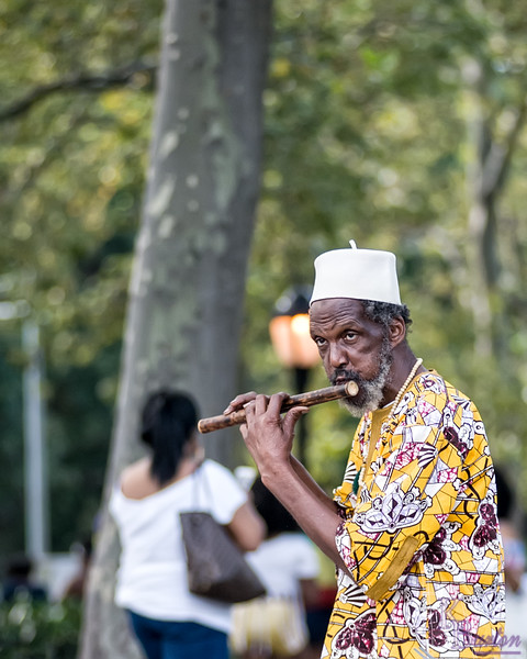 As I was walking back to the subway after the parade was over I spotted a man playing the flute, and saw another opportunity to test out my newly repaired 80-200mm lens.