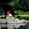 I came upon this scene one Sunday morning after taking a shot of City Hall Park at dawn. After taking that shot I purchased a take out lunch, and stopped by this pond to eat it for brunch, but first I had to grab a shot of this young woman reading her Sunday paper.<br /> <br />  If you've already looked at the shot of the two people sitting on that great looking wood bench that I took, (it's located earlier in this gallery), this woman is sitting less than 20 feet from it.