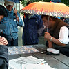 When I left my house this particular soggy morning, I wanted to capture some interesting moments in Chinatown that included umbrella's. So when I saw the match going on at this table I went straight for it. I wanted a shot of everyone looking at the chess board which was sopping wet from the rain, to increase the drama, but the man on the left was intently reading his newspaper instead. Given the amount of people around this particular table I guessed that it was a very good match, and that sooner or later the ebb and flow of the game would draw his attention back again, and he would finally put his paper down. My hunch was correct. Then I just waited for the player on the right to let out a nice long drag of cigarette smoke, which would stand out nicely because of the navy jacket behind it, if the man wearing it didn't move, which as fortune had it, he didn't. As soon as I snapped the shutter I knew I had one heck of a shot.