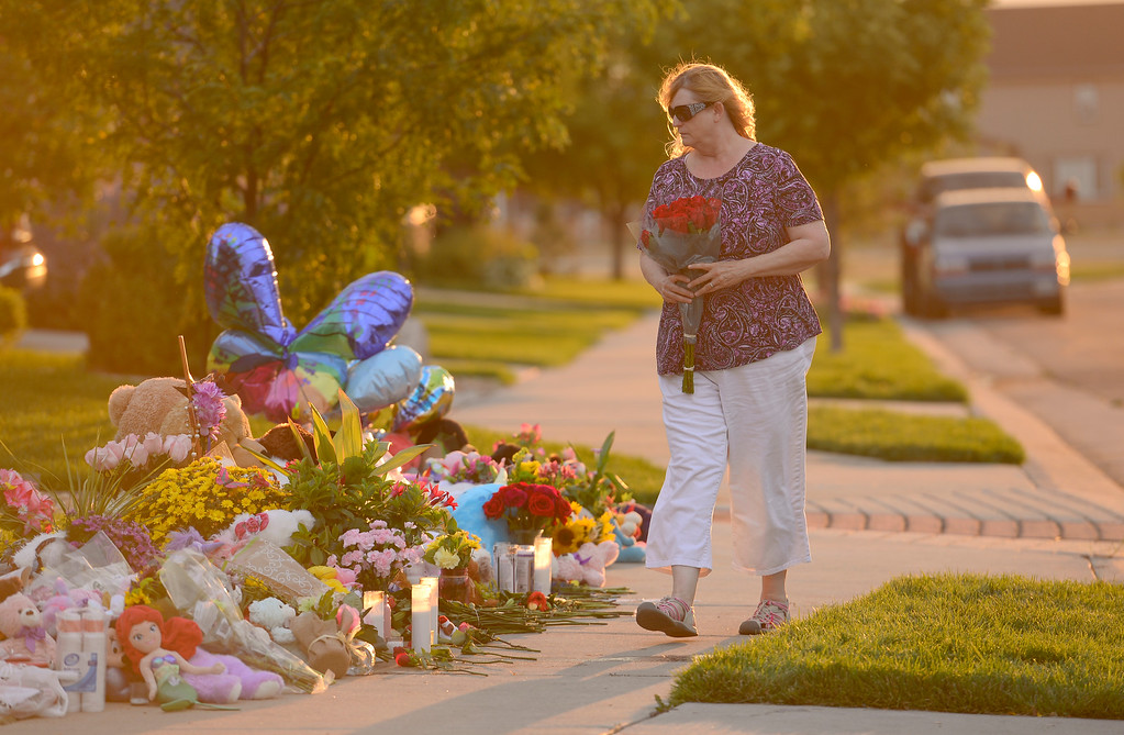 . FREDERICK, CO - AUGUST 17: Nancy Lee, of Evans, leaves flowers on a growing memorial for Shanann, Bella and Celeste Watts in front of their home on the 2800 Block of Saratoga Trail in Frederick on Aug. 17, 2018. Christopher Watts is being held without bond after allegedly admitting to killing his wife and daughters.  (Photo by Matthew Jonas/Staff Photographer)