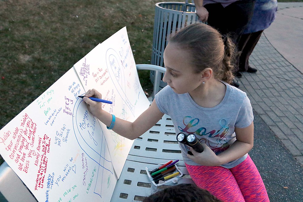 . Lexianna Paula, 9, of Leominster signs a poster at the candle light vigil for Sofia Brito, 6, who has passed away and Julian Brito, 9, who is still in the hospital on Friday night at Riverfront Park in Fitchburg. SENTINEL & ENTERPRISE/JOHN LOVE
