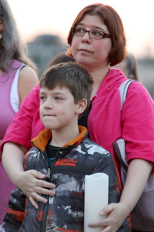 . Stephanie Ponusky and her son Tyler Ponusky, 8, both from Fitchburg listen to speakers at the candle light vigil for Sofia Brito, 6, who has passed away and Julian Brito, 9, who is still in the hospital on Friday night at Riverfront Park in Fitchburg. SENTINEL & ENTERPRISE/JOHN LOVE