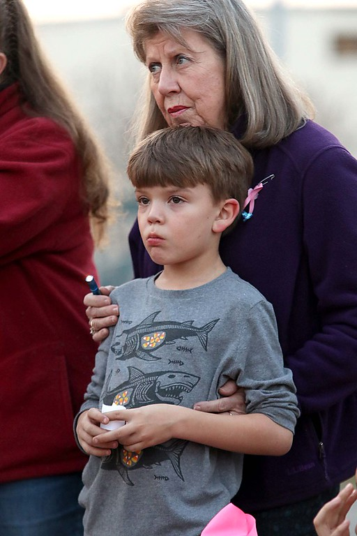 . Jane Keough from leominster and her grandson Preston Shorter, 9, from Fitchburg listen to speakers at the candle light vigil for Sofia Brito, 6, who has passed away and Julian Brito, 9, who is still in the hospital on Friday night at Riverfront Park in Fitchburg. SENTINEL & ENTERPRISE/JOHN LOVE