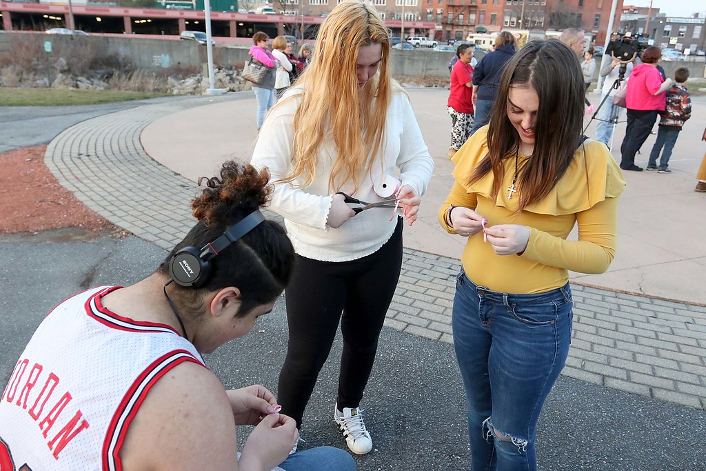 . Nate Perez, 18, Sammi Grant, 17, and Kendra Grant, 14, make ribbons at the candle light vigil for Sofia Brito, 6, who has passed away and Julian Brito, 9, who is still in the hospital on Friday night at Riverfront Park in Fitchburg. SENTINEL & ENTERPRISE/JOHN LOVE