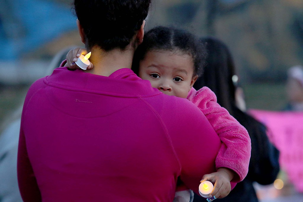 . Amaya Weekes, 2, holds some candles as her mom Tristan Peasley, both from Fitchburg, rocks her in her arms at the candle light vigil for Sofia Brito, 6, who has passed away and Julian Brito, 9, who is still in the hospital on Friday night at Riverfront Park in Fitchburg. SENTINEL & ENTERPRISE/JOHN LOVE