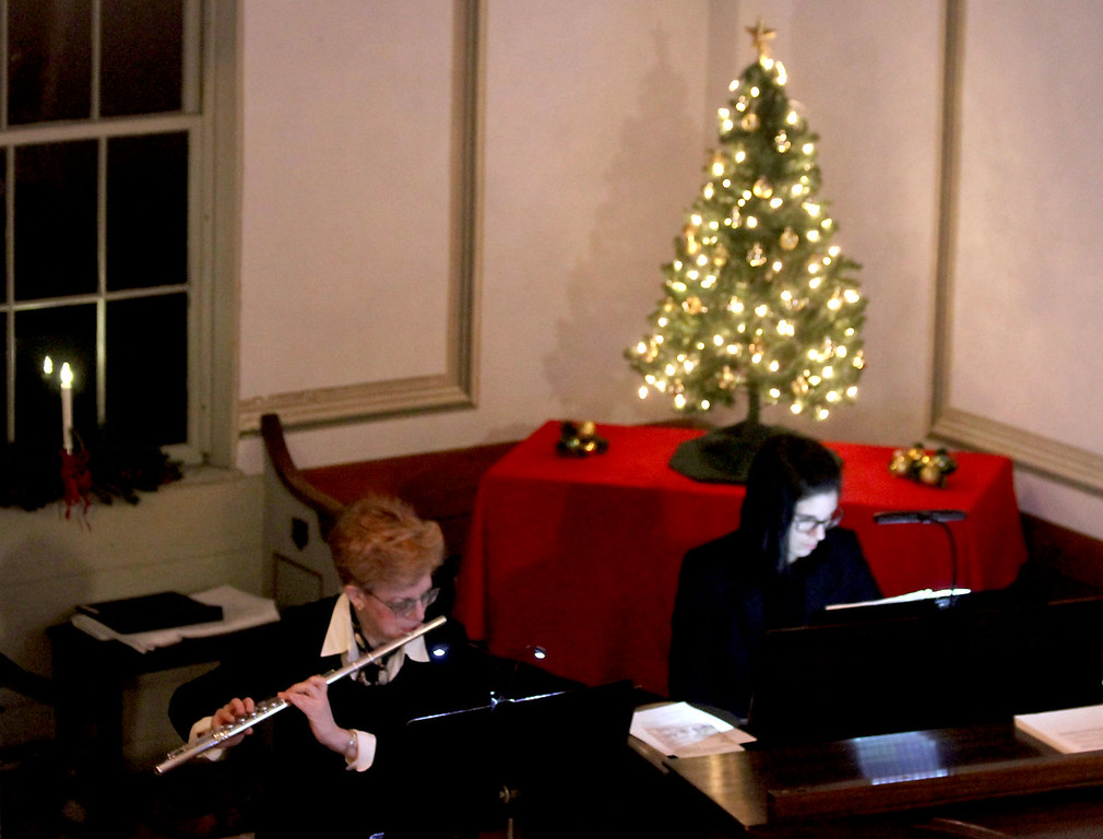 . Playing the flute is Laura Finkelstein and at the paino is Rene Minalga-Rheault for a selection in the Bringing Christmas Home program, part of the Candlelight Vespers at the Shirley Meeting House. Nashoba Valley Voice/David H. Brow