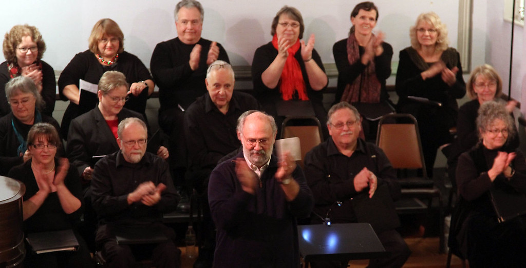 . Ronald Banay, middle, claps for the crowd as he welcomes folks to the Candlelight Vespers at the Shirley Meeting House on Sunday night. Nashoba Valley Voice/David H. Brow