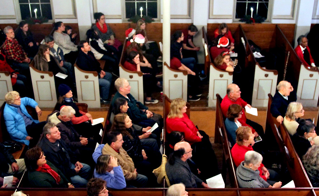 . Folks listen to the Bringing Christmas Home program during Candlelight Vespers at the Shirley Meeting House. Nashoba Valley Voice/David H. Brow