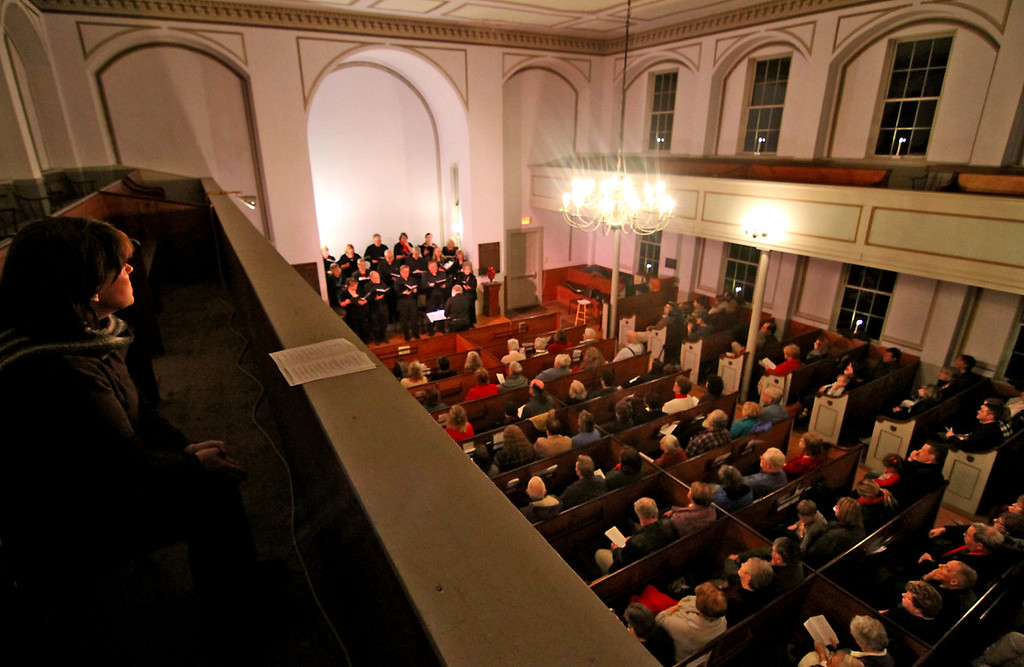 . Joanne Folkins of Shirley, sitting on left, listens to the Bringing Christmas Home program of Candlelight Vespers at a packed Shirley Meeting House on Sunday night. Nashoba Valley Voice/David H. Brow
