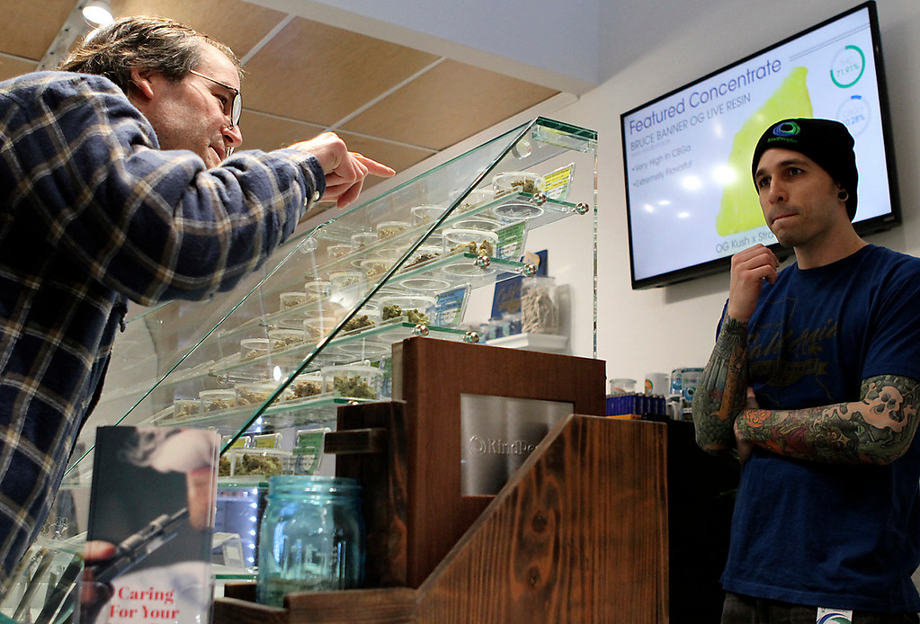 . Dan Matteson inquires about the properties of a variety of pot offered at KindPeoples Monday as Bryan Alfrey tends a station of the sales counter. (Shmuel Thaler -- Santa Cruz Sentinel)