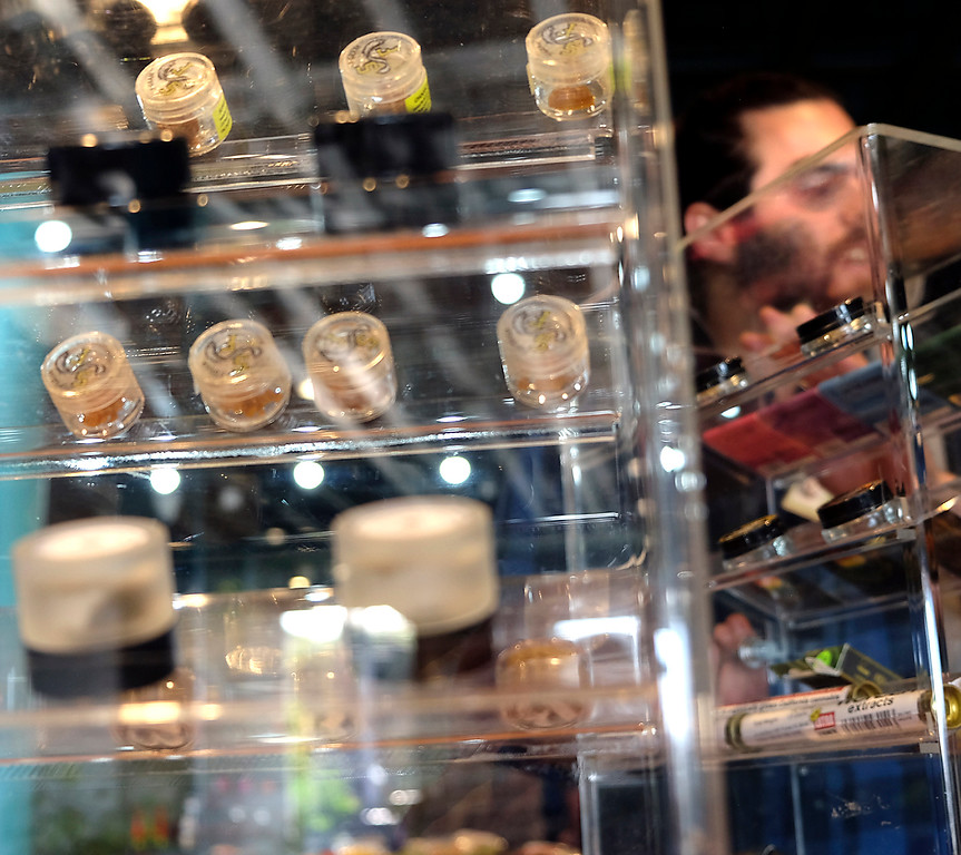 . Budtender Vini Gebrael is seen through displays of product at Treehouse pot dispensary in Soquel on Monday. (Shmuel Thaler -- Santa Cruz Sentinel)