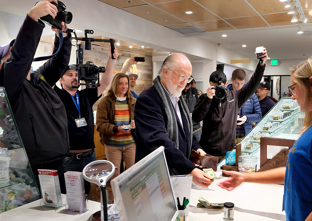 . UC Santa Cruz sociology professor emeritus Craig Reinarman is surrounded by members of the media as he makes the first purchase of legal marijuana at KindPeoples marijuana dispensary on Monday.. (Shmuel Thaler -- Santa Cruz Sentinel)