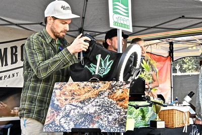 Evan Moore of Canna Graphics adjusts his micro-lens camera up to take a ultra-high resolution picture of a cannabis leaf. The photograph in the foreground is a close-up of THC crystals formed on a tight cannabis bud. (Jose Quezada - For the Times-Standard)