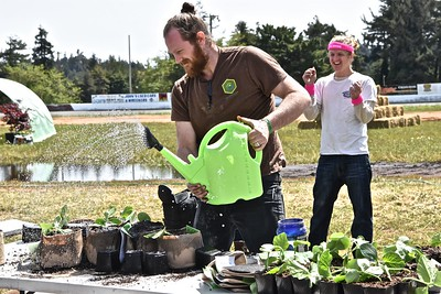 """Angus Funkhouser of True Humboldt competes in the Transplanting section of the Humboldt Grow Games competition held in the racetrack area Saturday afternoon. Standing behind Funkhouser is Jon-Luke """"Captain"""" Pickard, cheering his Growship Enterprise teammate Tim """"Beardley"""" Glick (not pictured). (Jose Quezada - For the Times-Standard)"""