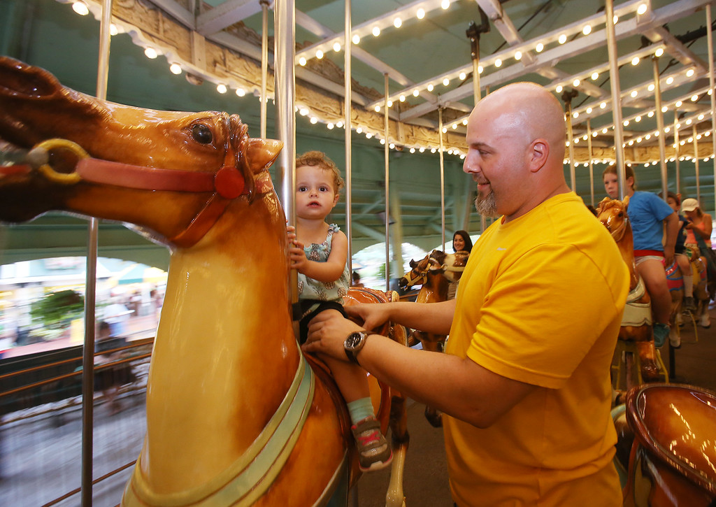 . James St. Hilaire of Londonderry, N.H., with daughter Chloe St. Hilaire, 2, on the Carousel at Canobie Lake Park in Salem, N.H. (SUN/Julia Malakie)