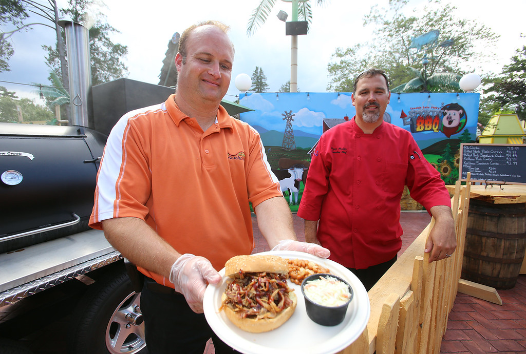 . Canobie Lake Park in Salem, N.H. Garett Borrows of Hampstead, N.H., general manager of food & beverages for Sodexo, left, and Bryan Moshier of Concord, N.H., executive chef for Canobie Lake Park, with pulled pork plate at the new Smokin\' BBQ. (SUN/Julia Malakie)