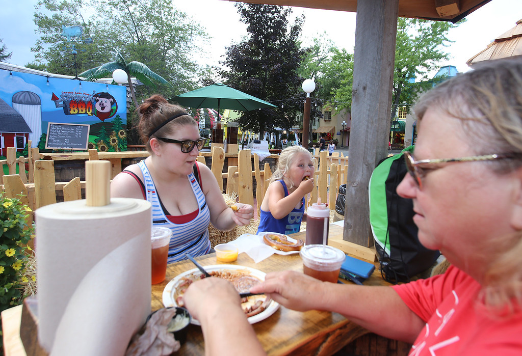 . Canobie Lake Park in Salem, N.H. From left, Becky Ross, her daughter Alexa Finchum, 7, and her mother Kathy Kenyon, all of Clinton, eat at the new Smokin\' BBQ. (SUN/Julia Malakie)