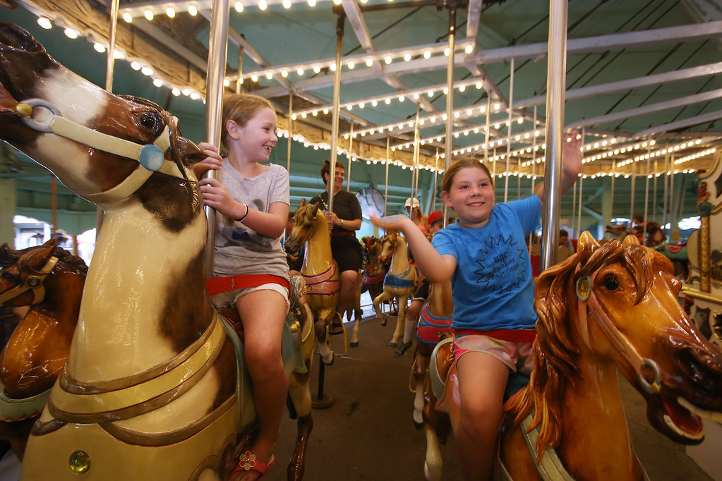 . Ari Symonds, left, and Emma Donnelly, both 8 and from Arlington, ride the historic Carousel at Canobie Lake Park in Salem, N.H.  (SUN/Julia Malakie)