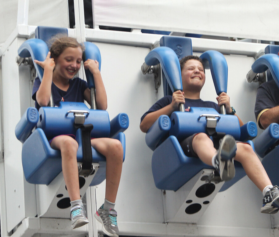 . Canobie Lake Park in Salem, N.H. Ava Cottreau, left, and Mikey Imbrascio, both 9 and from Billerica, ride the Starblaster, which involves rapid drops. (SUN/Julia Malakie)