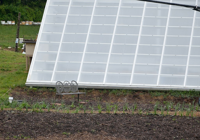 The Roper/YMCA gardens' solar greenhouse with bench and flower garden in front honoring Emily Cottingham Stuart.<br /> April 26, 2012