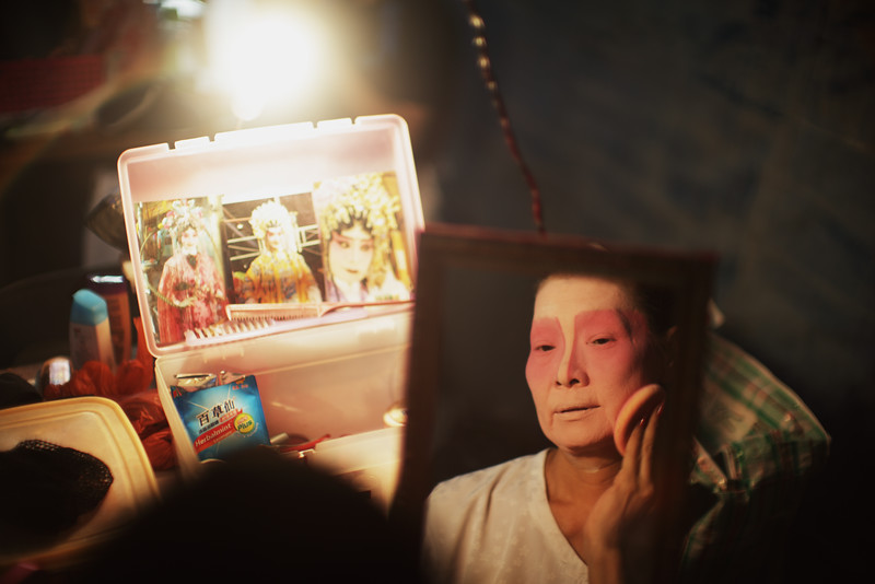 """In the shortlived transitory phase between unembellished reality and full-fledged fantasy, drawing inspiration from portraits of operatic heroines pasted in her personal makeup box. Lao Sai Tao Yuan Teochew Opera Troupe on Pulau Ubin.<br><span style=""""font-size:75%"""">©Yangchen Lin</span>"""