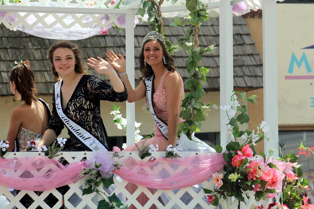 . The Blossom Festival\'s queen Alessandra Giammo, right, rides in a float with first attendant Nicole Bechtel, left, and other members of Blossom Royalty Saturday during the parade.