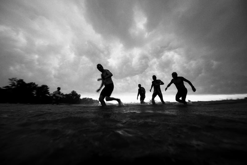 """Tri-Factor triathlon 2016. Swimmers make a beeline for the shore as a tropical thunderstorm closes in, shortly before the suspension of the race. Bedok Jetty can just be made out in the distance.<br><span style=""""font-size:75%"""">©Yangchen Lin</span>"""