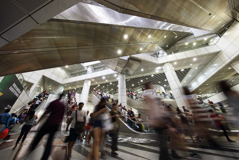 """Rush hour at Dhoby Ghaut MRT station. At least ten escalators criss-cross this underground confluence of the North-South, North-East and Circle lines.<br><span style=""""font-size:75%"""">©Yangchen Lin</span>"""