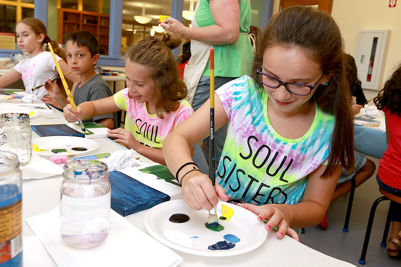 The Leominster Public Library held a canvas painting workshop with local artist Jen Niles on Tuesday, July 25, 2017 in the childrens room at the library. Ava Macone, 9, and her friend Tessa DiVerdi, 9, get ready to paint the grass part of their painting. SENTINEL & ENTERPRISE/JOHN LOVE