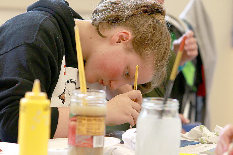 The Leominster Public Library held a canvas painting workshop with local artist Jen Niles on Tuesday, July 25, 2017 in the childrens room at the library. Sadie Michelson, 11, works diligently on her painting during the class. SENTINEL & ENTERPRISE/JOHN LOVE