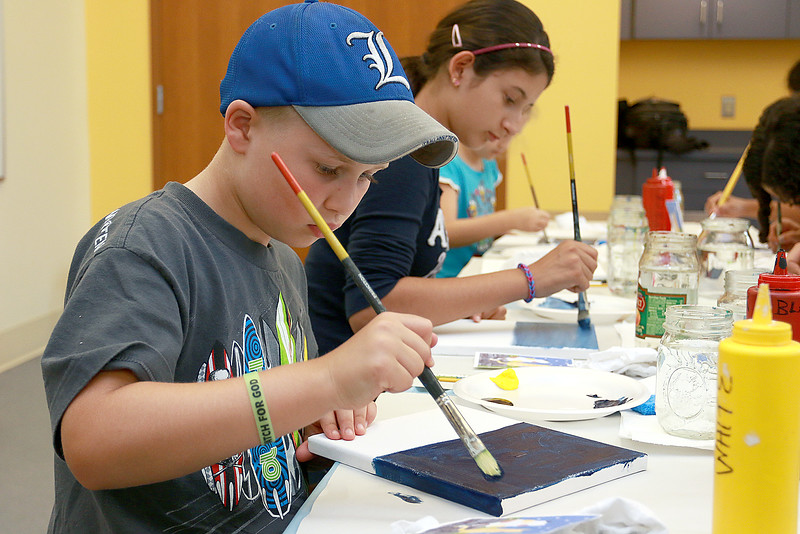 The Leominster Public Library held a canvas painting workshop with local artist Jen Niles on Tuesday, July 25, 2017 in the childrens room at the library. Nicholas Luzzetti, 8, works on painting the sky part of his painting. SENTINEL & ENTERPRISE/JOHN LOVE