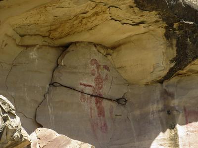 Nearby is a kokopelli pictograph.  A cable has been attached so the rock does not fall and break.
