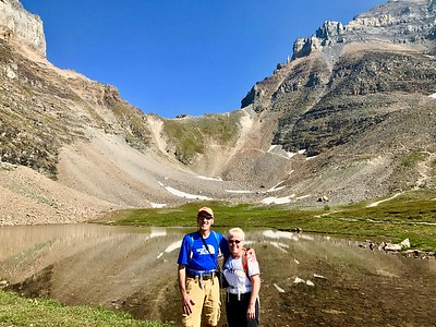 """08/09/17: A picture of us taken after hiking down from Sentinel Pass. We were told this specific hike is considered one of the """"Top Ten"""" most beautiful hikes in the world and equally challenging, which it definitely was on both counts! In the background you can see the trail with the long and steep switchbacks. Directly behind us is Minnestimma Lake."""