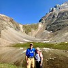 """08/09/17: A picture taken of us when we were heading down after hiking Sentinel Pass. We were told this specific hike is considered one of the """"Top Ten"""" most beautiful hikes in the world and equally challenging, which it definitely was on both counts! In the background you can see the trail switchbacks and directly behind us is Minnestimma Lake."""