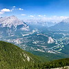 08/05/17: This is a view of Banff from the summit of Sulphur Mountain. In the middle of the photo is Tunnel Mountain, 5,344'. In the front of Tunnel Mountain is the Fairmont Banff Springs Hotel. On the right of Tunnel Mountain is the Bow River, which runs through the town of Banff. In the upper background is Two Jack Lake and behind it is the larger, glacial Lake Minnewanka. The high peak in the upper left is Cascade Mountain, 9'835'.