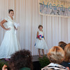 Desi Smith/Cape Ann<br /> Here comes the bride in a wedding dress made from recycled spinnaker sailcloth, designed by Frieda Grotjahn of Again and Again in Gloucester. Modeled by Colleen Lally of Gloucester is embellished with delicate hand-cut sailcloth flowers with iridescent sequin centers, and the neckline and sleeve edges are trimmed with scalloped, handmade sailcloth lace. The bride'sbouquet of flowers is made from sailcloth with delicate pink centers. Lotus Marsh's  tea-length flower girl dress has a full skirt and bodice overlay made from recycled spinnaker sailcloth.